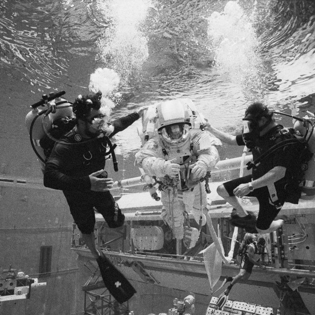 NASA NBL Safety DIvers guide the Astronaut crew member to the downline for descent.