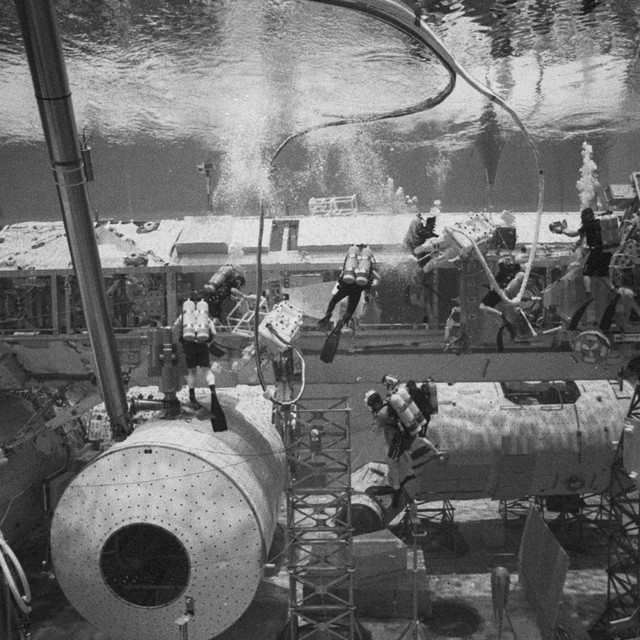 The two NASA crew members translate down the truss to begin work while the safety divers constantly monitor their status.